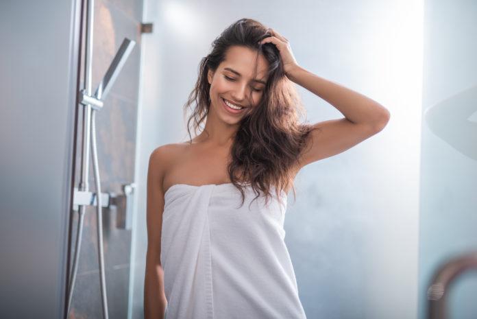 uśmiechnięta kobieta owinięta w ręcznik kąpielowy