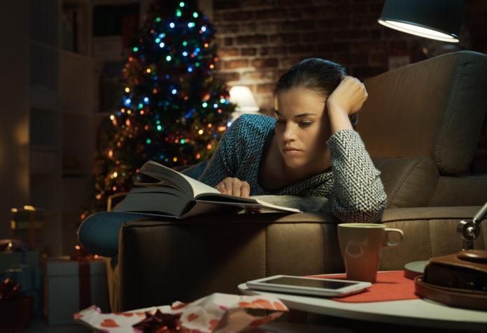 kobieta czytająca ksiązkę przy choince