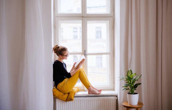 kobieta w oknie czytająca książkę