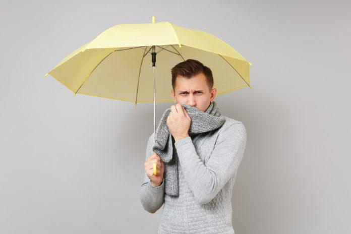 mężczyzna pod żółtą parasolką