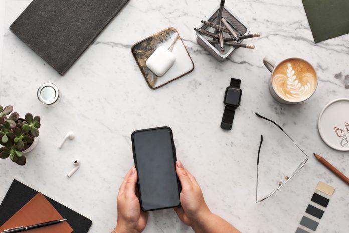 praca ze smartfonem przy biurku