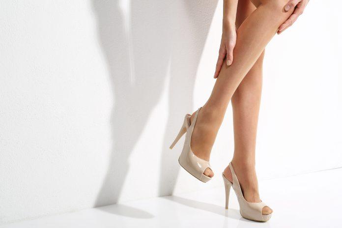 Bolące nogi, cały dzień w szpilkach. Nogi kobiety w rajstopach.