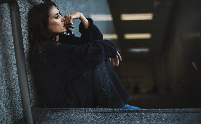 smutna kobieta siedząca na schodach metra