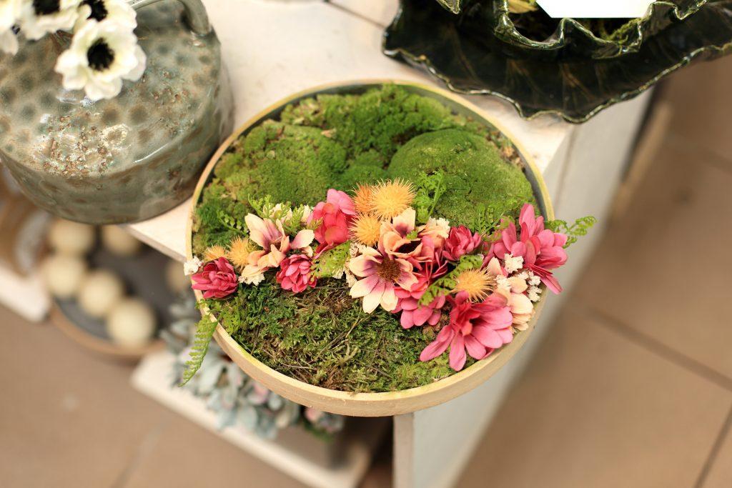 Stroik, dekoracja z kwiatów i mchu w drewnianym talerzu.
