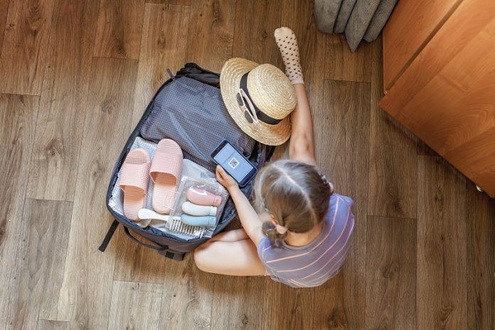 dziecko pakujące klapki na basen do walizki
