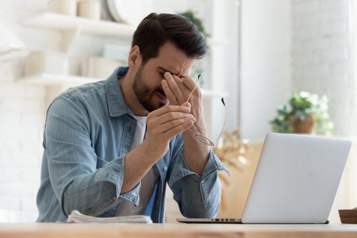 zmęczony mężczyzna przy laptopie