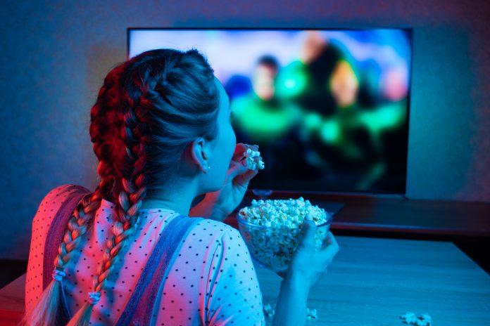 dziewczyna z popcornem oglądająca telewizję